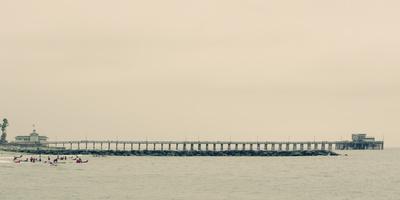 https://imgc.allpostersimages.com/img/posters/surfers-in-front-of-pier-in-newport-beach_u-L-Q1BB7JB0.jpg?p=0