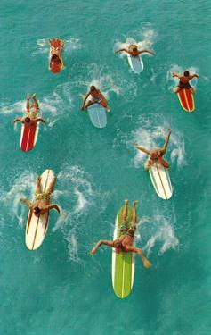Surfers Paddling on Multi-Colored Boards, from Above