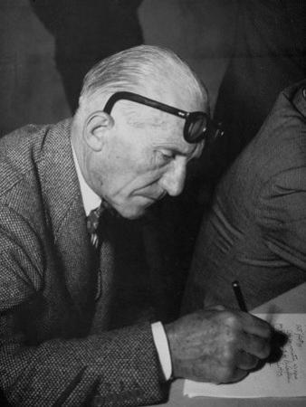 Swiss Architect Le Corbusier Leaning Down to Write with His Glasses Pushed Back on His Forehead