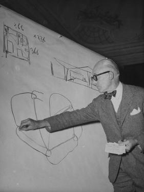 Swiss Architect Le Corbusier Standing on Stage with Notes in His Hand and Drawing on Sketch Pad
