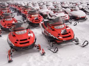 A Row of Snowmobiles Sit Waiting for the Next Adventure to Start by Taylor S. Kennedy