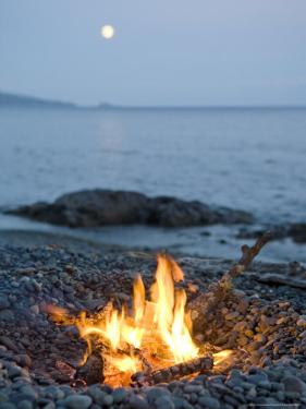 Campfire on a Beach with a Full Moon Visible by Taylor S. Kennedy
