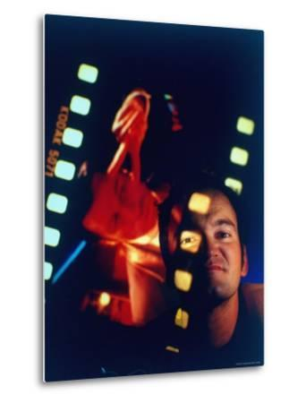 """Film Director Quentin Tarantino Framed by Projected Clip From His Movie """"Pulp Fiction"""" by Ted Thai"""