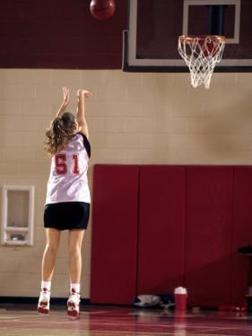Teenage Girl Practicing Basketball Indoors