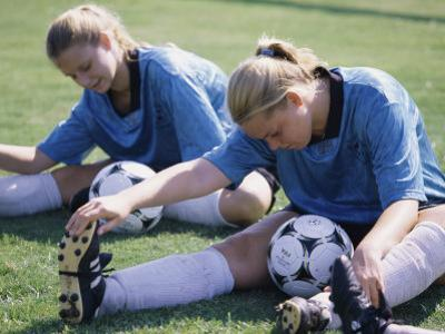 Teenage Girls in Soccer Uniforms Doing Stretching Exercises