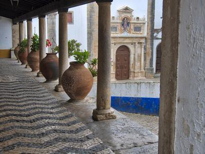 Portugal, Obidos. Ceramic pots adorning a building ledge.