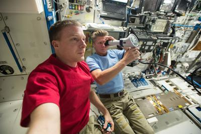 Astronaut and Cosmonaut Gennady Padalka Conduct an Eye Scan with a Fundoscope by Terry Virts
