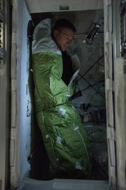 Astronaut Straps Himself into His Compartment to Sleep on the Iss by Terry Virts