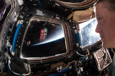 Astronaut Views His Multicolored Reflection in the Smudged Cupola Window by Terry Virts
