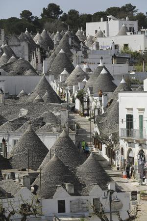 https://imgc.allpostersimages.com/img/posters/the-cone-shaped-roofs-of-trulli-houses-in-the-rione-monte-district-alberobello-apulia-italy_u-L-PWFELV0.jpg?p=0