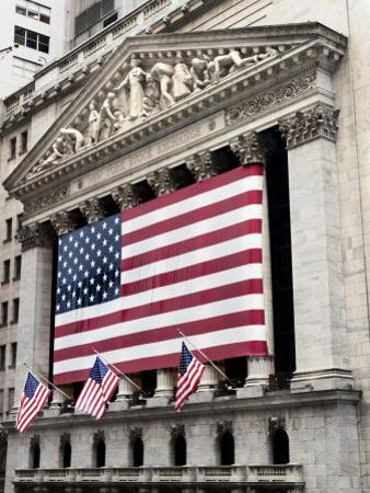 The facade of the New York Stock Exchange draped in the American Flag