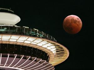 The Full Moon Turns Red and Orange as It Passes the Space Needle