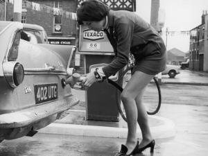 The Modern Female Petrol Pump Operator Refuelling a Car in Her Mini Skirt