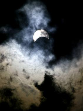 The Moon Partially Covers the Sun Behind the Clouds During a Partial Solar Eclipse