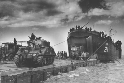 """The U.S. Coast Guard Manned USS LST-21 Unloads British Army Tanks and Trucks onto a """"Rhino"""" Barge"""