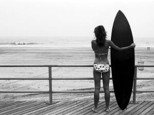 Model with Black Surfboard Standing on Boardwalk and Watching Wave on Beach by Theodore Beowulf Sheehan