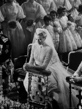 Actress Grace Kelly in Gorgeous Wedding Gown Praying During Her Wedding to Prince Rainier