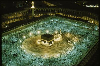 Thousands of pilgrims circle the Kaaba. by Thomas J. Abercrombie