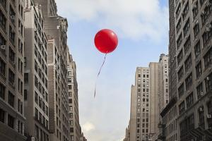 Red Balloon Floating through City by Thomas Jackson