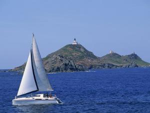 Sailing Boat with the Semaphore Lighthouse Behind, Iles Sanguinaires, Island of Corsica, France by Thouvenin Guy