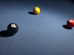 Three Billiard Balls on Blue Felt Pool Table