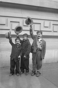 Three Boys (6-9) Wearing Fake Moustaches Waving Hats