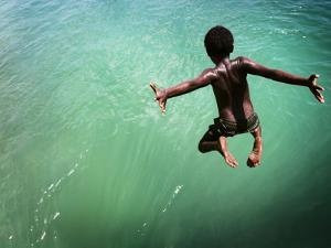 Torres Strait Islander Boy Leaping into the Sea, Seisia, Cape York by Tim Barker