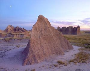 Crescent moon over landscape showing erosional features, Badlands National Park, South Dakota by Tim Fitzharris