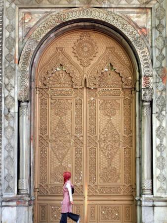 Young Turkish Woman Walking Past an Ornate Doorway in Ortakoy
