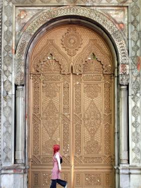 Young Turkish Woman Walking Past an Ornate Doorway in Ortakoy by Tim Hughes