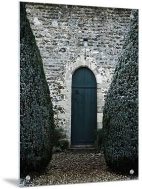 Stone Entry and Wood Door Flanked by Manicured Bushes by Tim Kahane