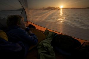 7 year old waking up at sunrise in tent on the in the mangroves. by Tim Laman