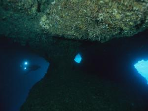 A Diver Explores an Underwater Formation Known as the Blue Hole by Tim Laman