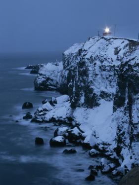 A Lighthouse Atop Snow-Covered Cliffs on Notsuke Bay by Tim Laman