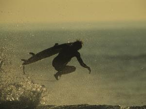 A Surfer and His Board Leap over Breaking Surf by Tim Laman