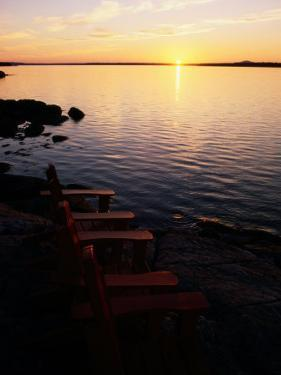 Two Empty Wooden Chairs Sit on Maine's Rocky Coast as the Sun Sets over the Horizon by Tim Laman