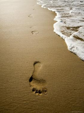 Waves About to Wash over Footprints in the Sand, Anaho Bay, French Polynesia by Tim Laman