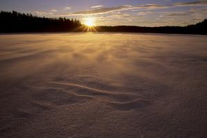 Winter sunset as seen from the frozen Walden Pond. by Tim Laman
