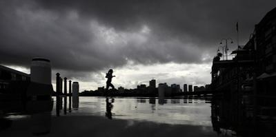 A Lunch-Hour Jogger Runs Along a Harbourside Wharf as a Thunderstorm Breaks over Central Sydney