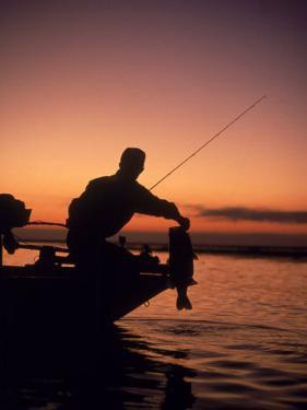 Silhouette of Bass Fisher at Sunset by Timothy O'Keefe