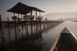 A Boat Glides Past a Wooden Bridge across Inle Lake at Dawn by Tino Soriano