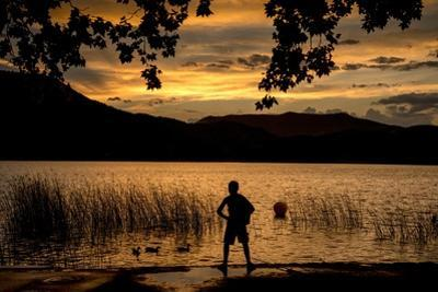 A boy's silhouette at sunset after a rain by Tino Soriano