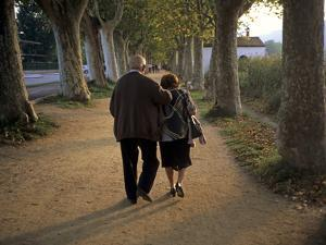 An Elderly Couple Walking Along a Tree-Lined Dirt Road by Tino Soriano