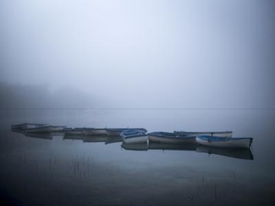 Boats in calm waters on a foggy day. by Tino Soriano