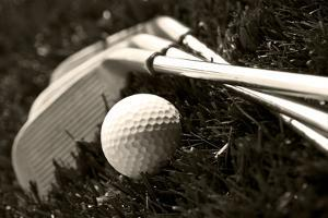 Black And White Photo Of Golf Clubs And A Golf Ball In Low Light For Contrast by tish1