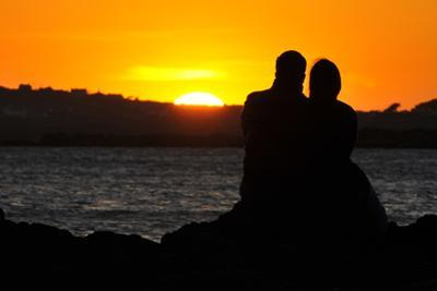 A Couple Watch the Sun Setting on a Beach Near Holyhead in Anglesey, North Wales