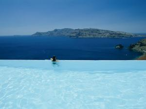 A Swimmer Enjoys the View from a Pool Overlooking the Aegean by Todd Gipstein
