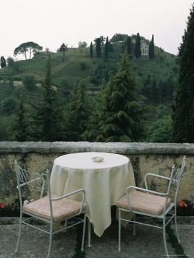 Cafe Table and Chairs Overlooking a Villa on a Hill by Todd Gipstein