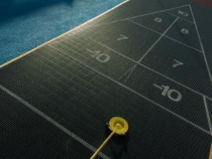 Setting up for a Shot on a Shuffleboard Game on a Cruise Ship by Todd Gipstein