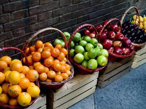 Six Baskets of Assorted Fresh Fruit for Sale at a Siena Market, Tuscany, Italy by Todd Gipstein